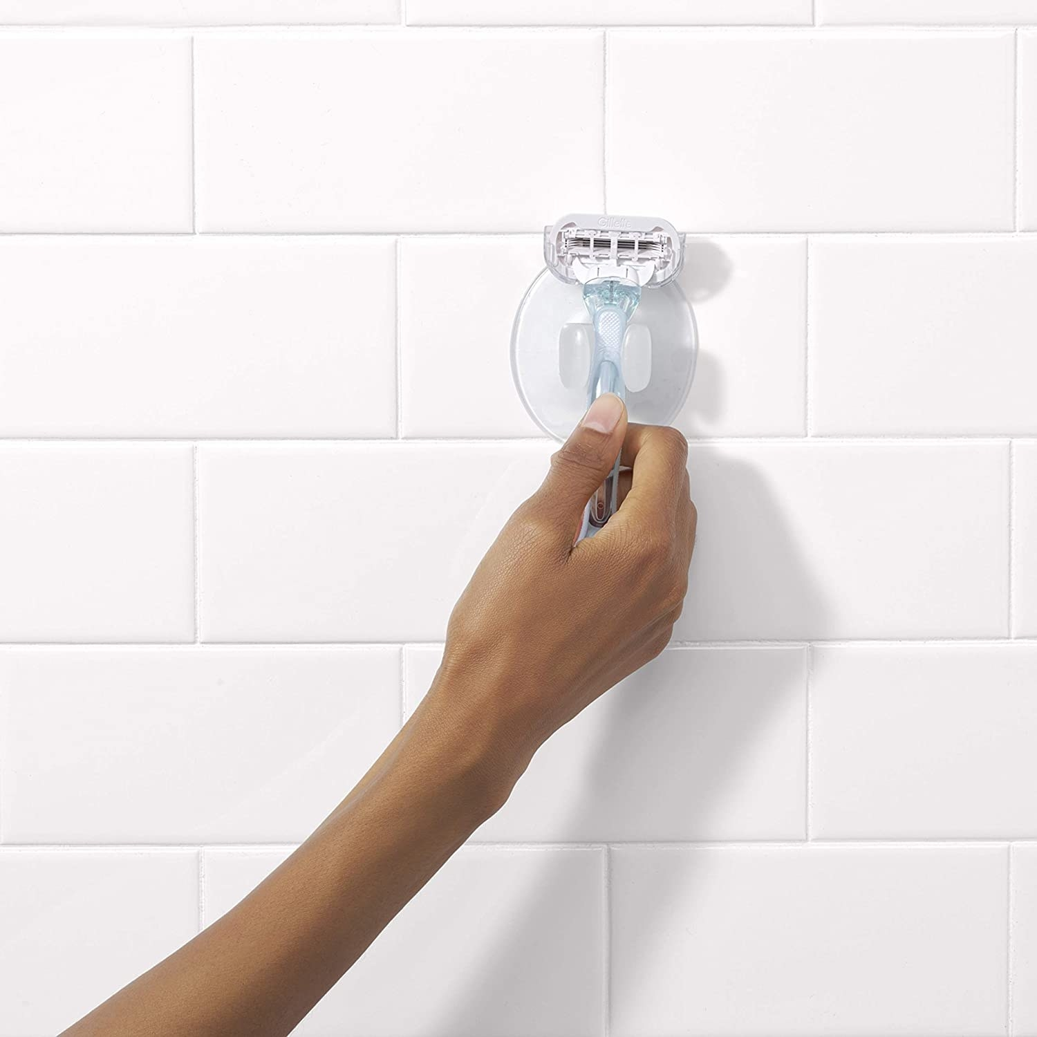 the suction on a wall with someone putting the razor in it