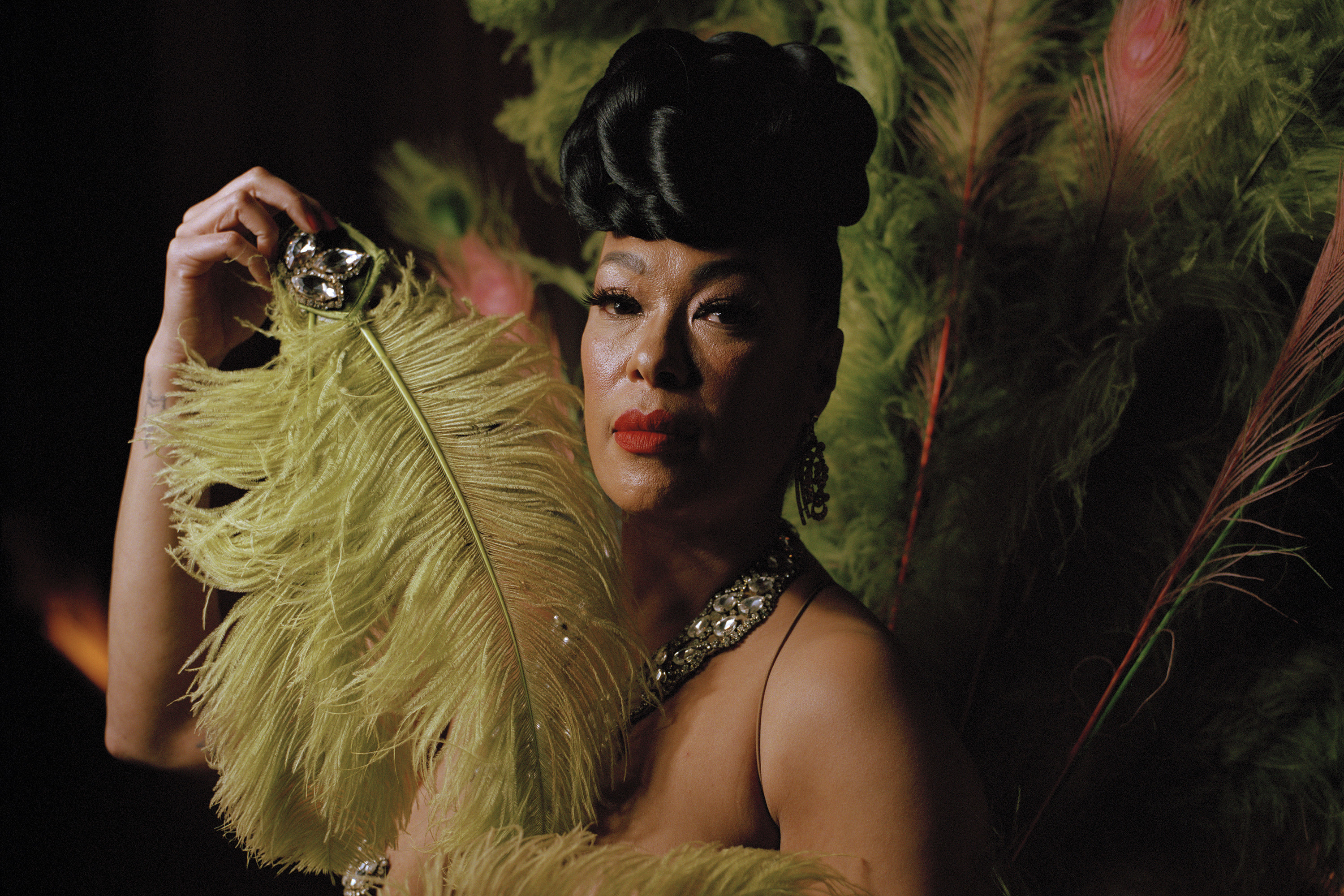 Burlesque dancer Maine Attraction holding up large a feather near her face
