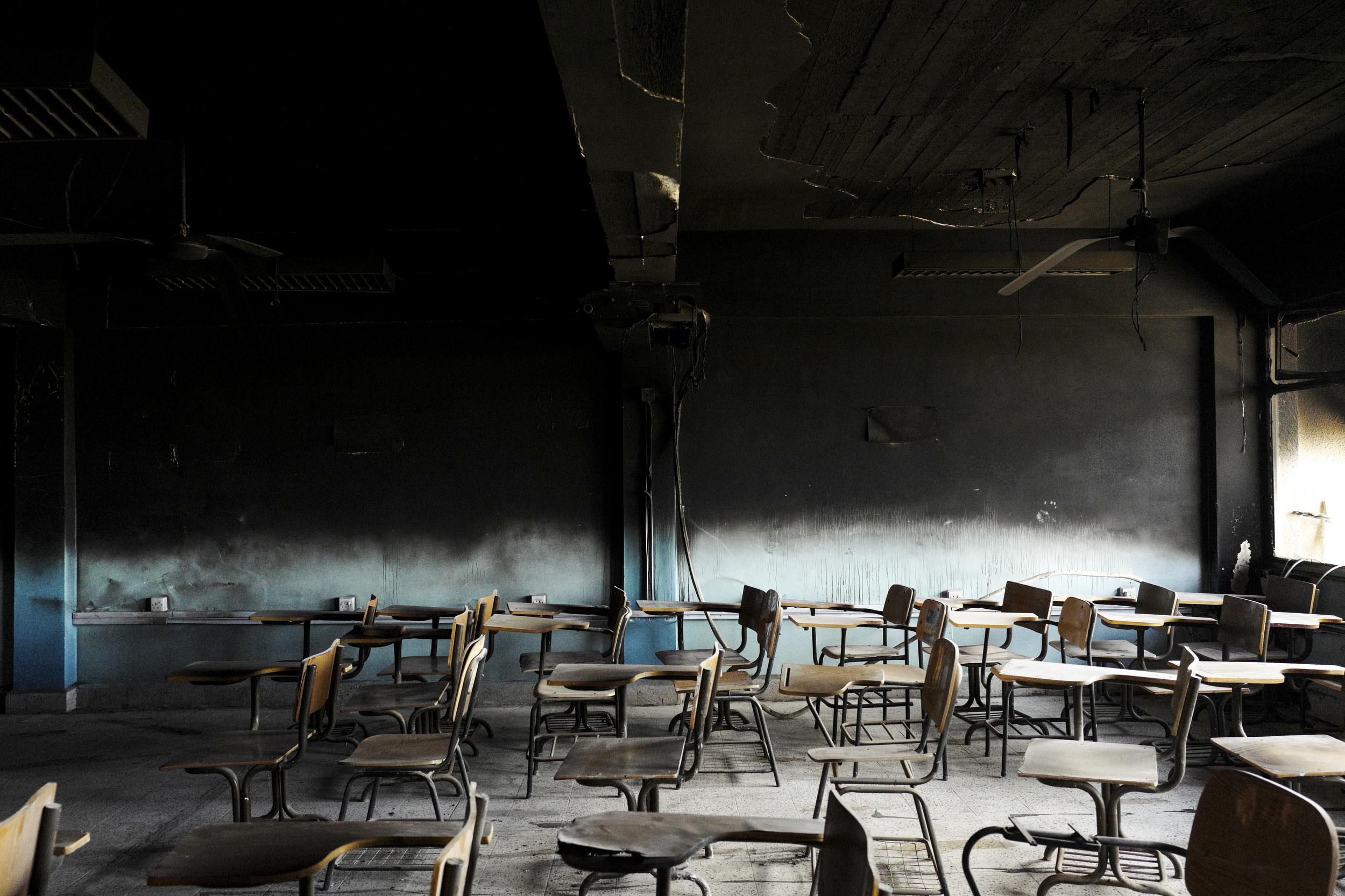 An empty school room with desks out of order and charred walls