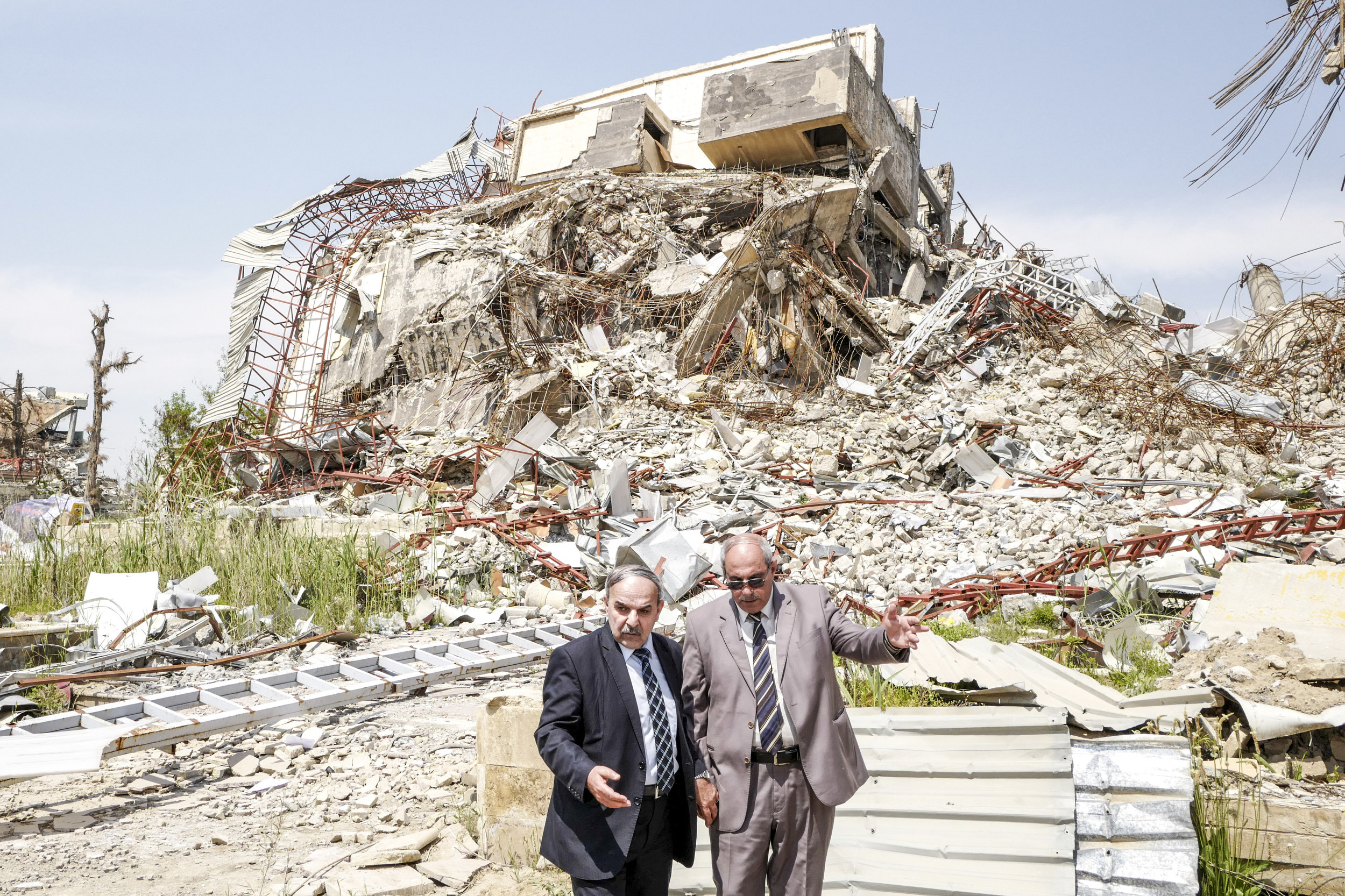 Two men in suits in front of a massive pile of rubble