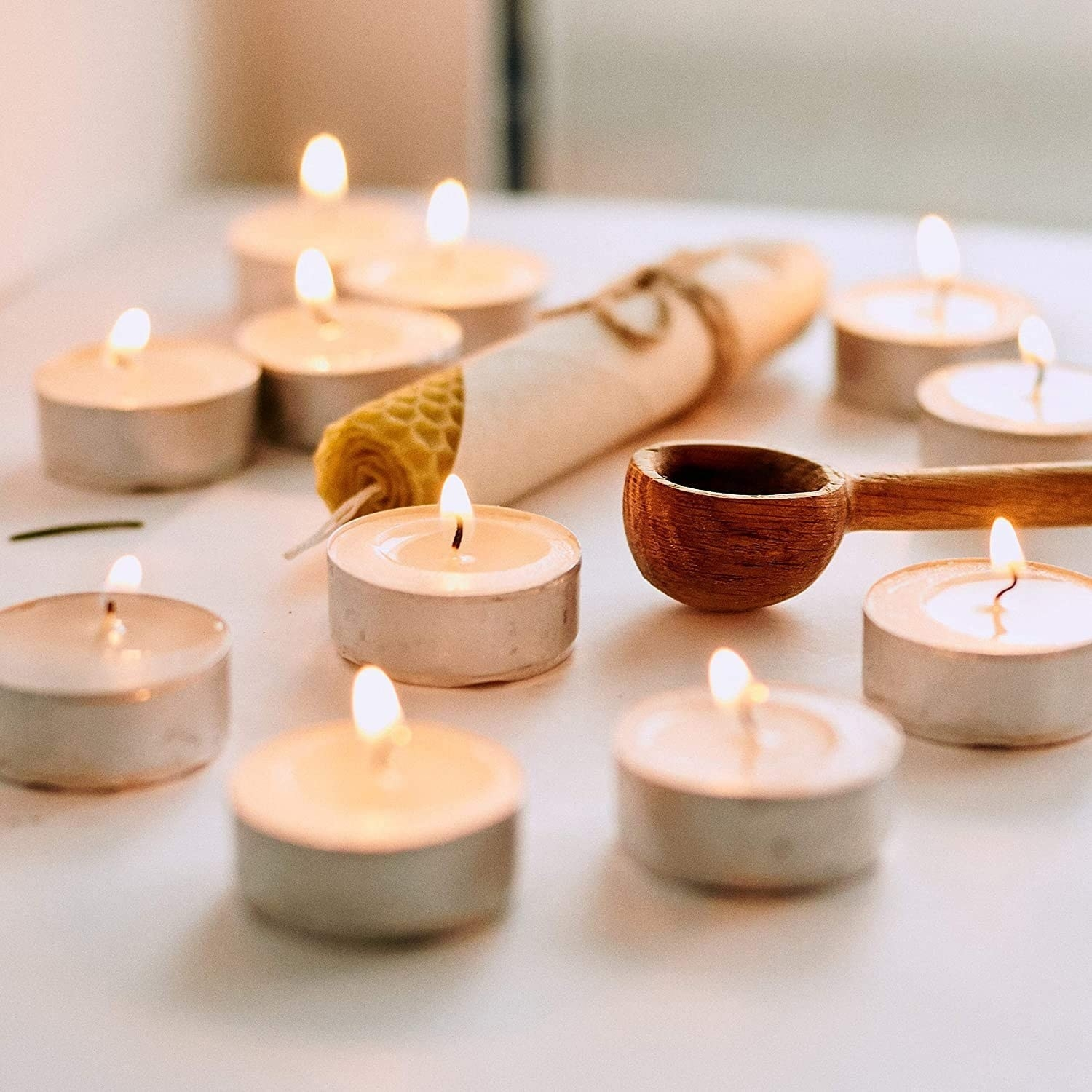 Several tiny candles aflame beside a wooden spoon and beeswax