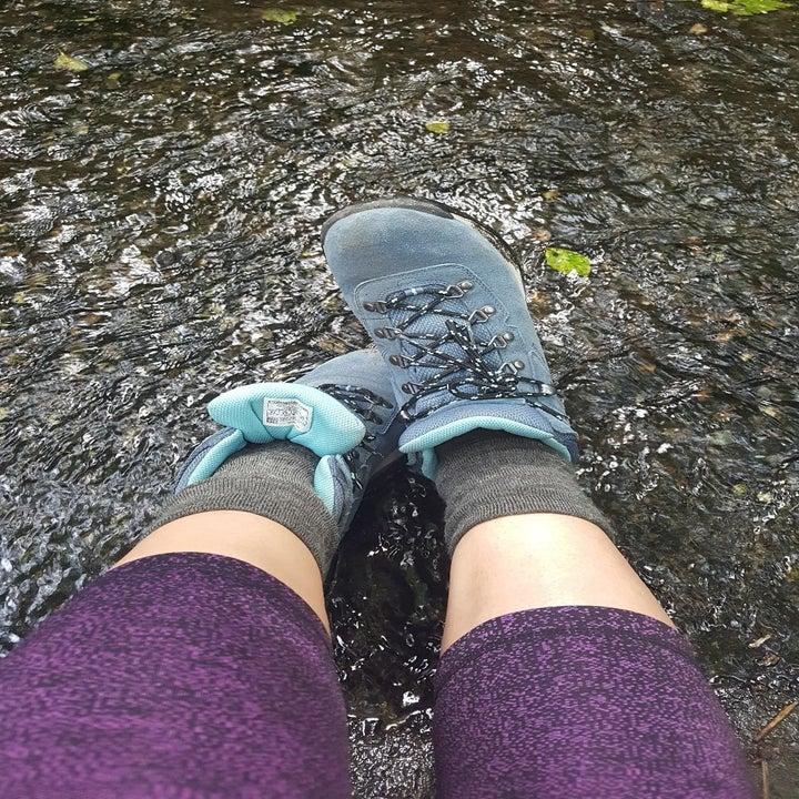 reviewer wears same hiking boot in a blue shade while relaxing by a stream