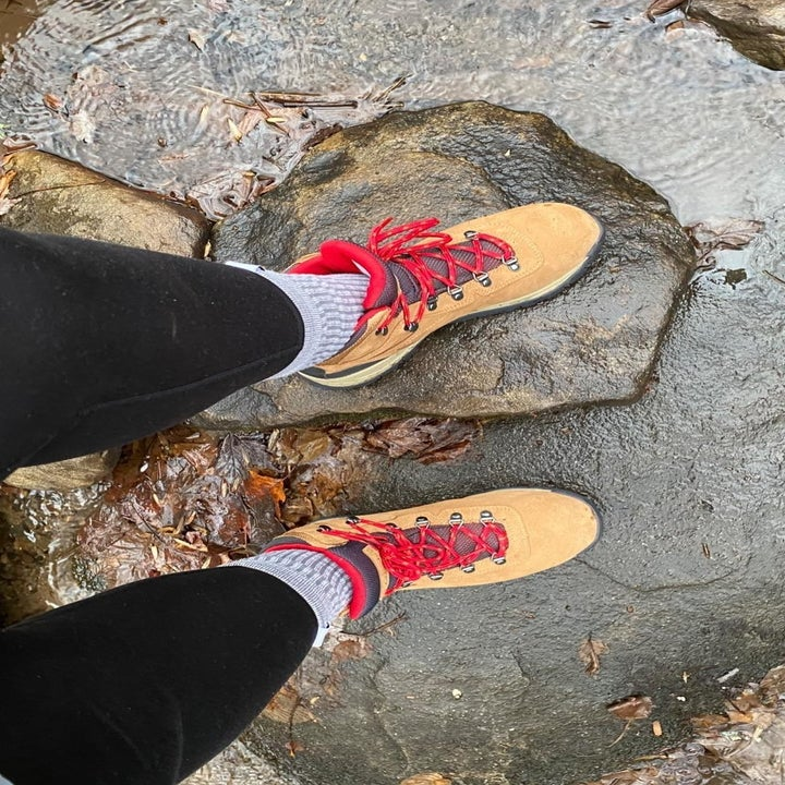 reviewer wears tan hiking boots while walking across rock area with water