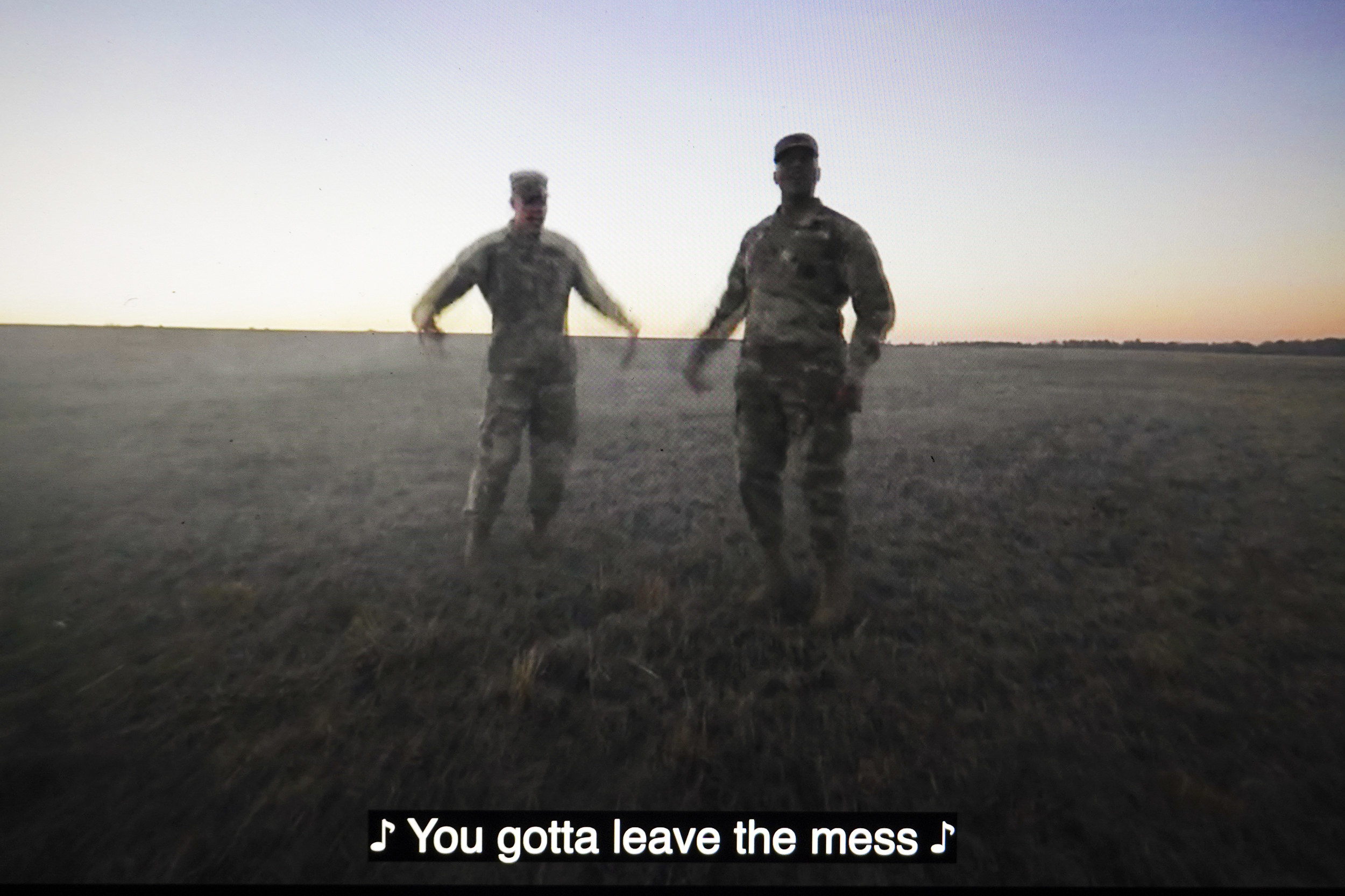 "Two men in fatigues dancing in a  video with closed captioning that reads ""You gotta leave the mess"""