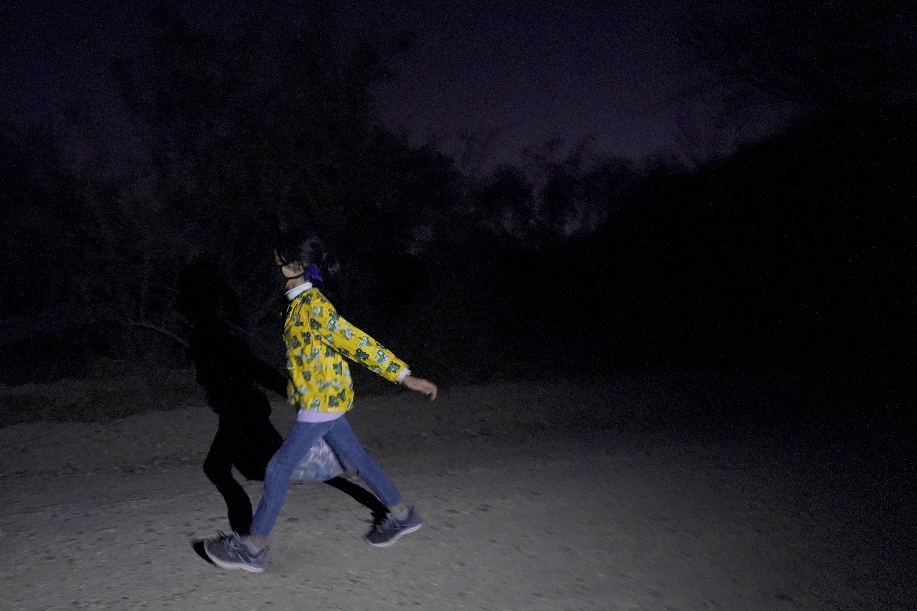 A young girl walks quickly on a path at night