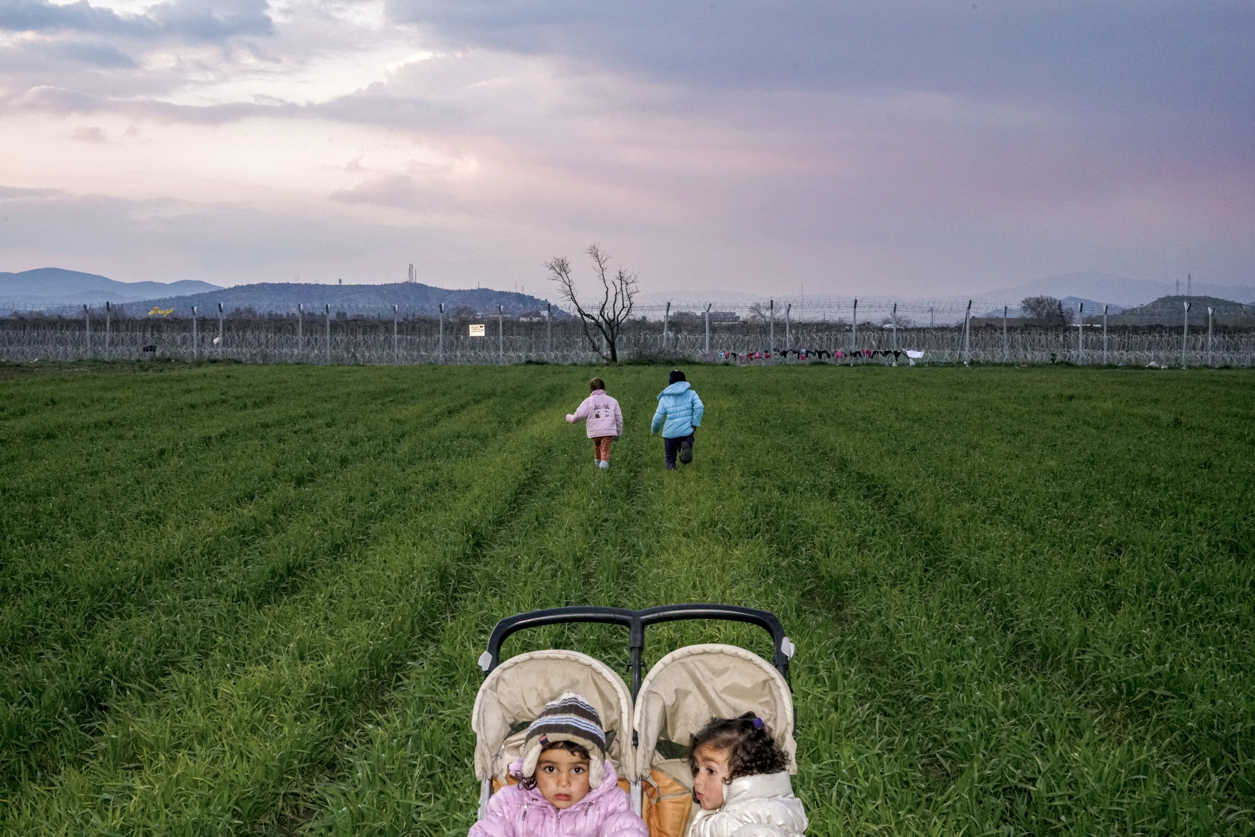 two small children in a push chair while their mothers walk in a field behind barbed wire
