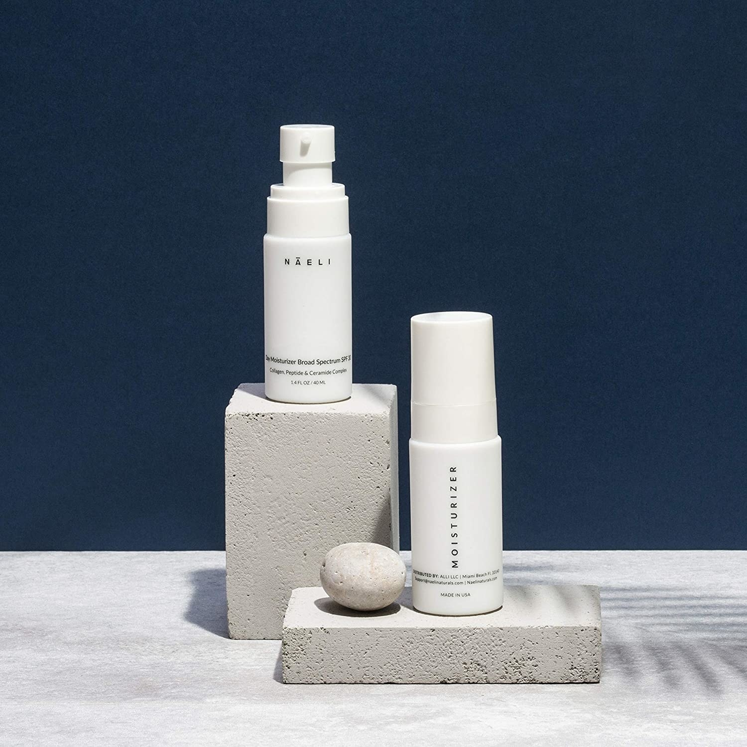 two bottles of Naeli Face Moisturizer with SPF 30 atop cement display stands