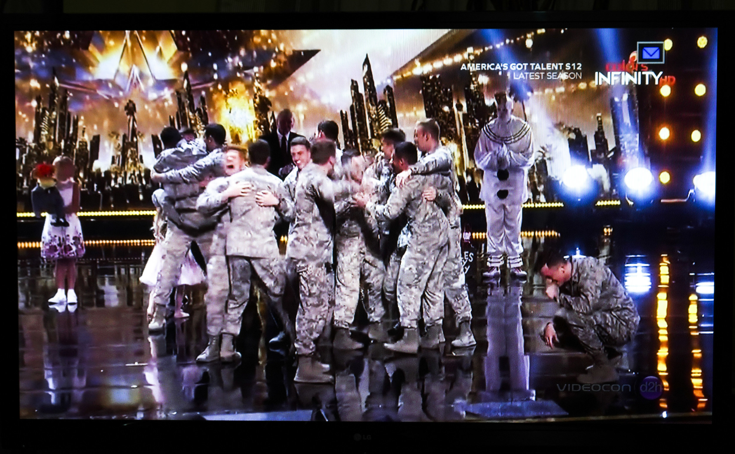 A television screen with a group of men all hugging each other in combat fatigues