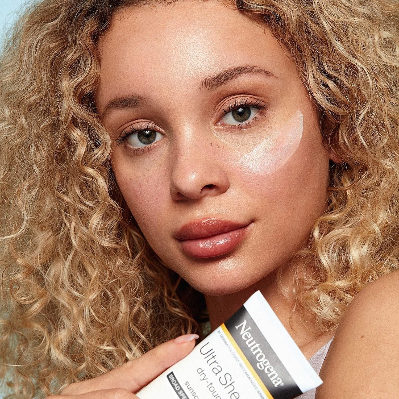 Model holding bottle of Neutrogena dry-touch sunscreen