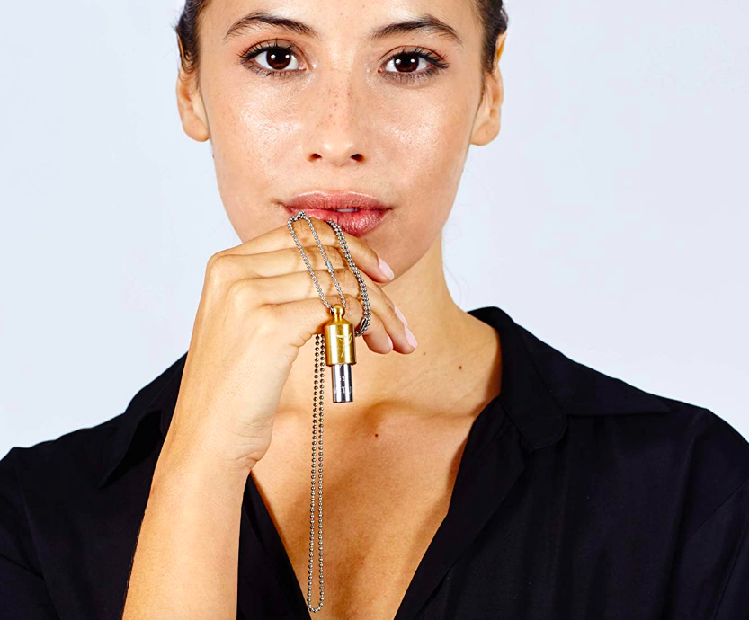 Model holding whistle-like necklace on a chain