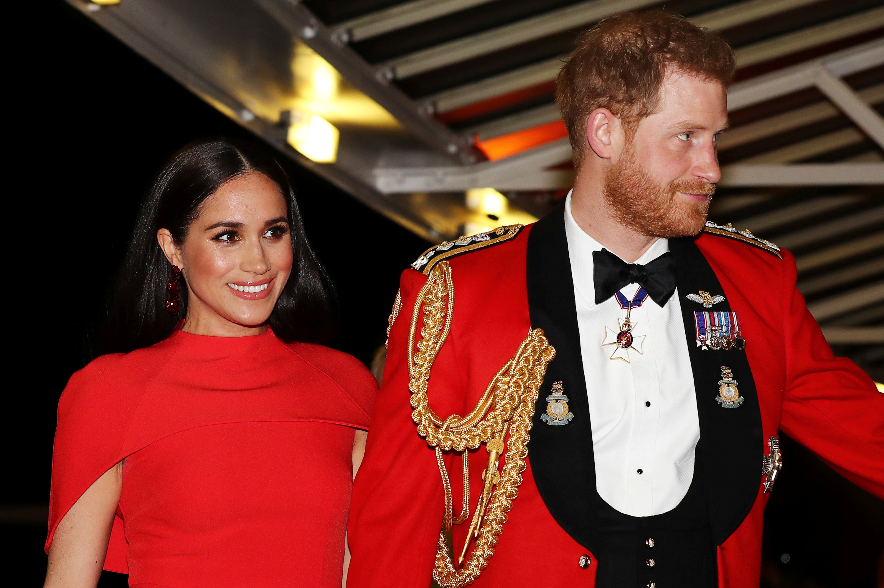 Meghan smiles in a red dress at a formal event with Harry