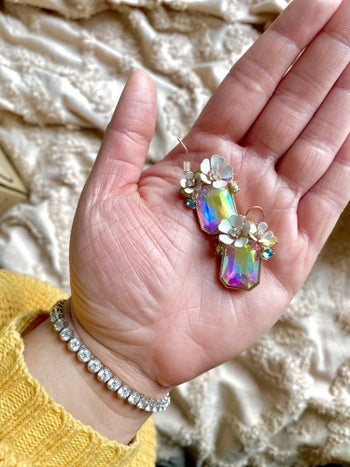 Buzzfeed editor holding the iridescent gem earrings in her hand