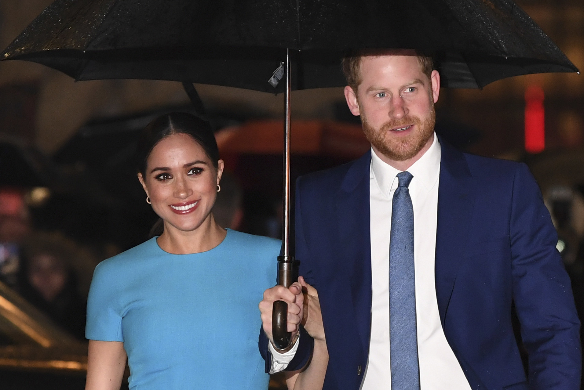 Meghan smiles next to Prince Harry while standing under an umbrella