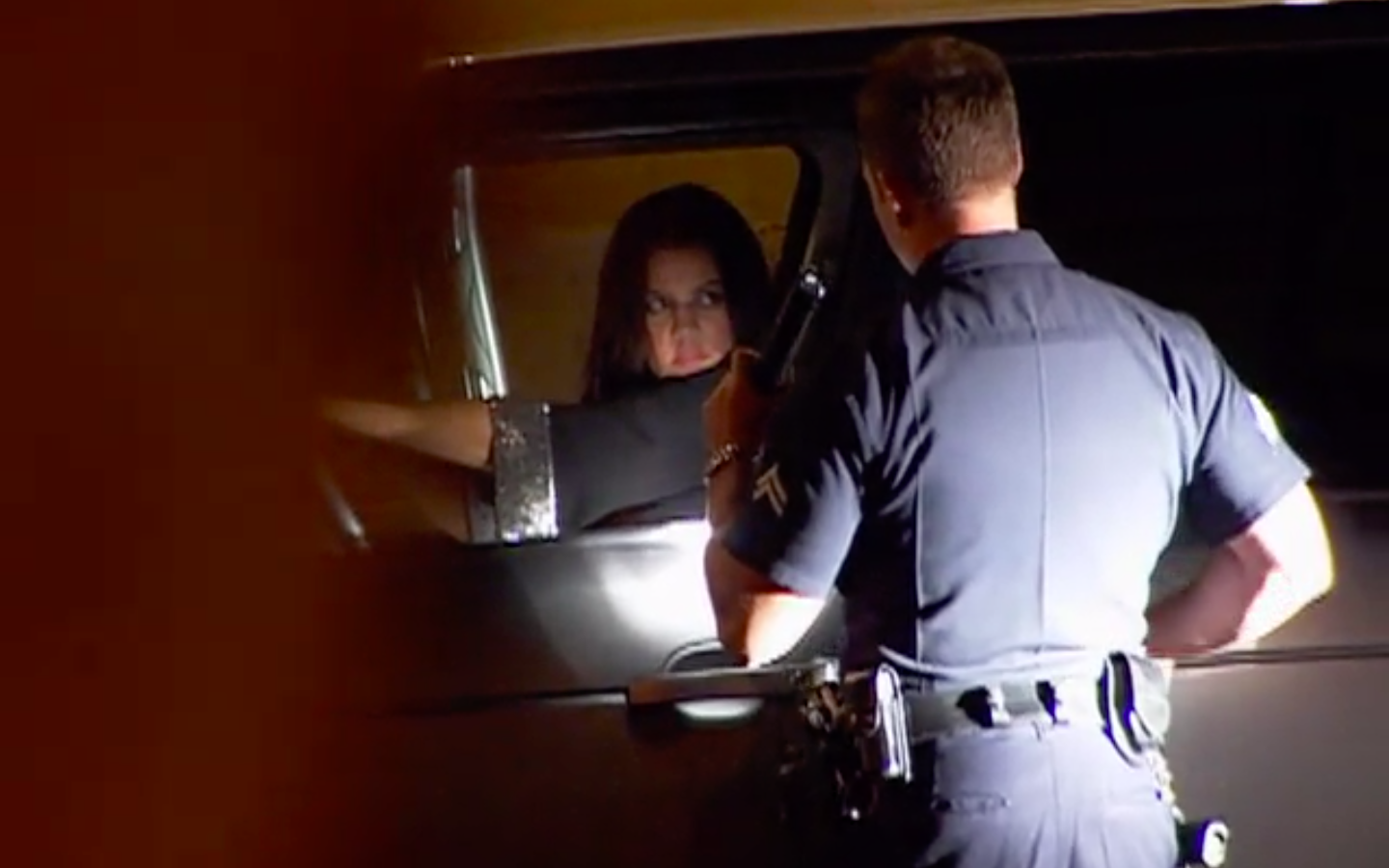 A police officer holds a flashlight up to Khloé in her car