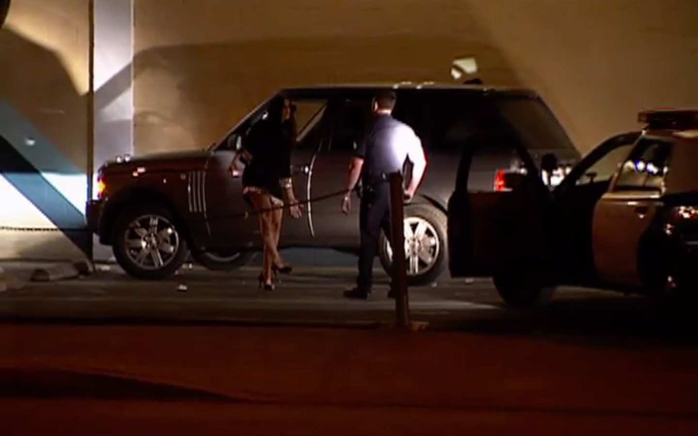 A screenshot shows Khloé walking in a line during a sobriety test outside of her car with a police officer