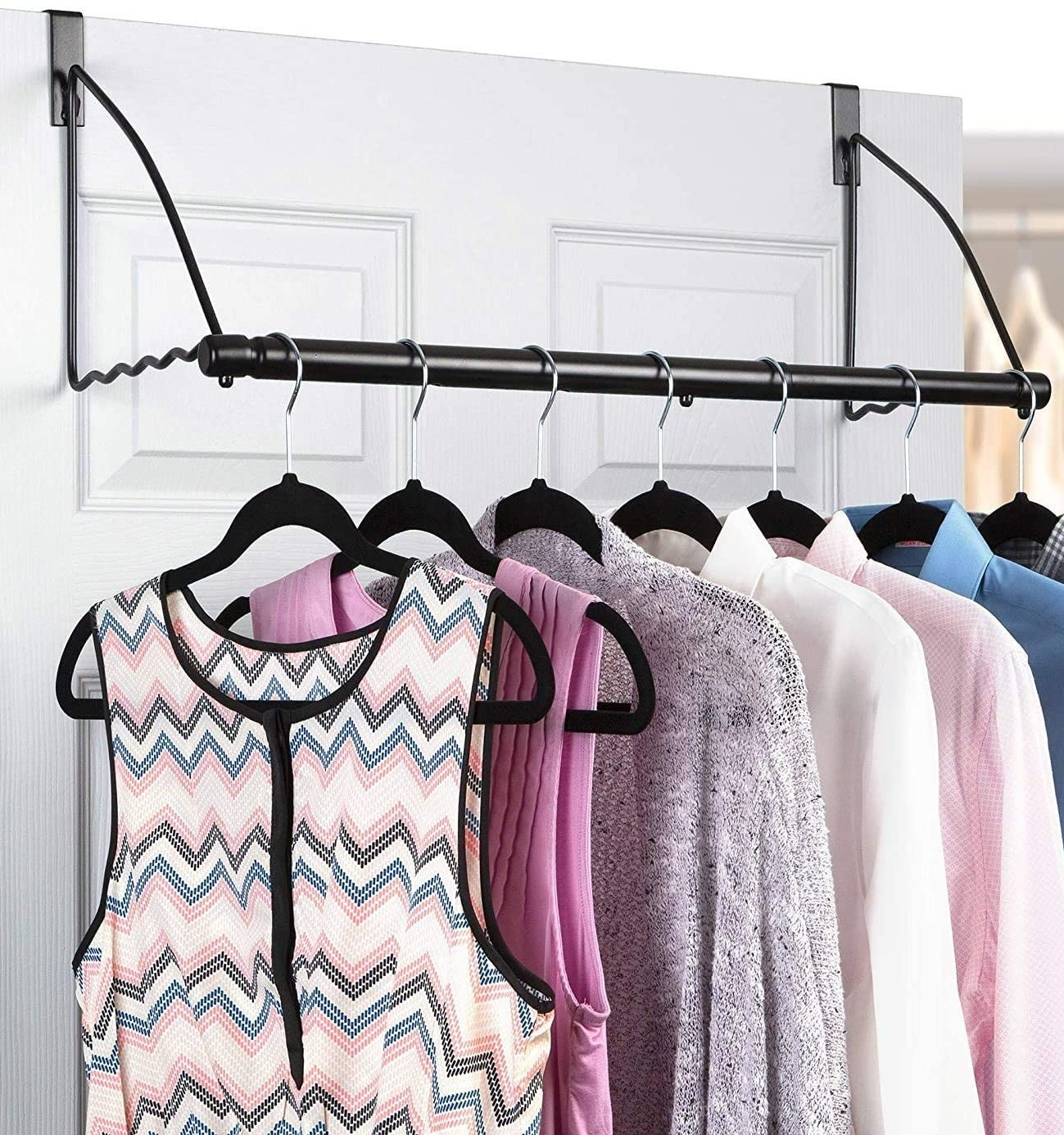 Several shirts hanging from the rod