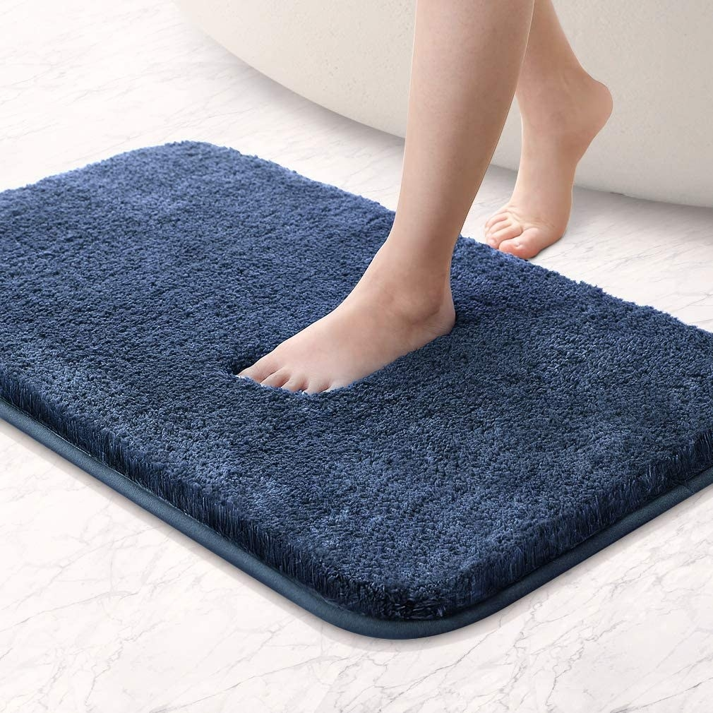 A person stepping onto the bath mat