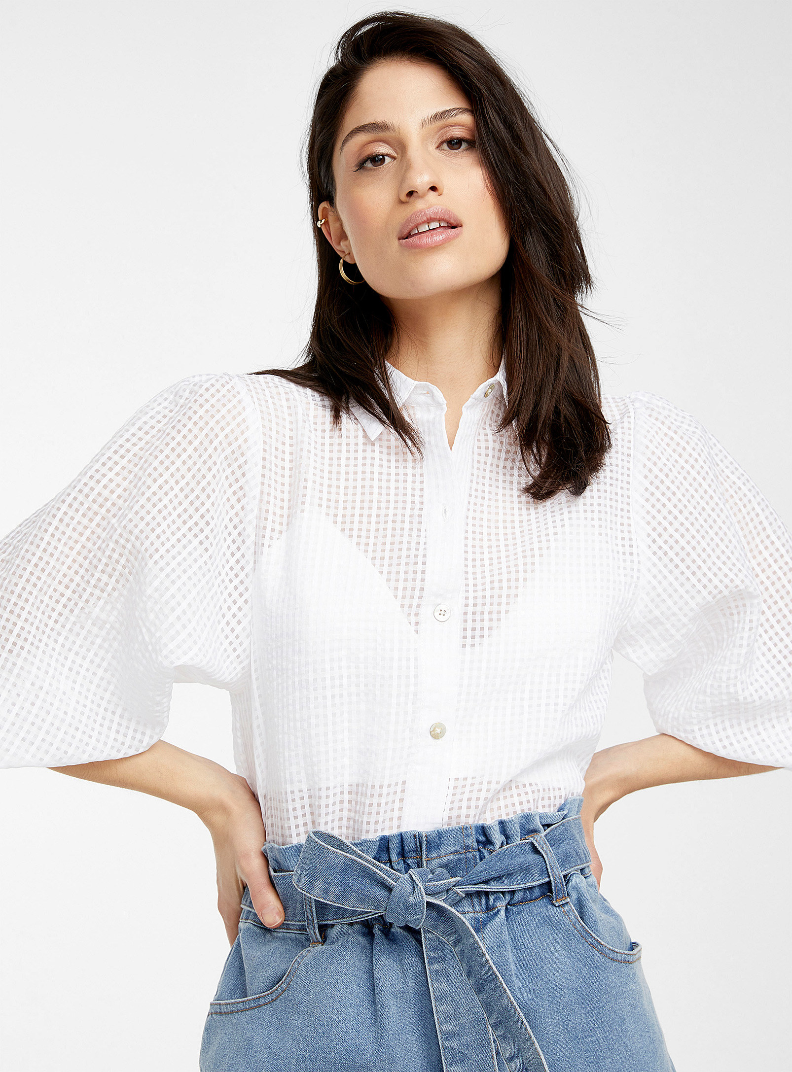 A person wearing a button-up shirt with oversized sleeves
