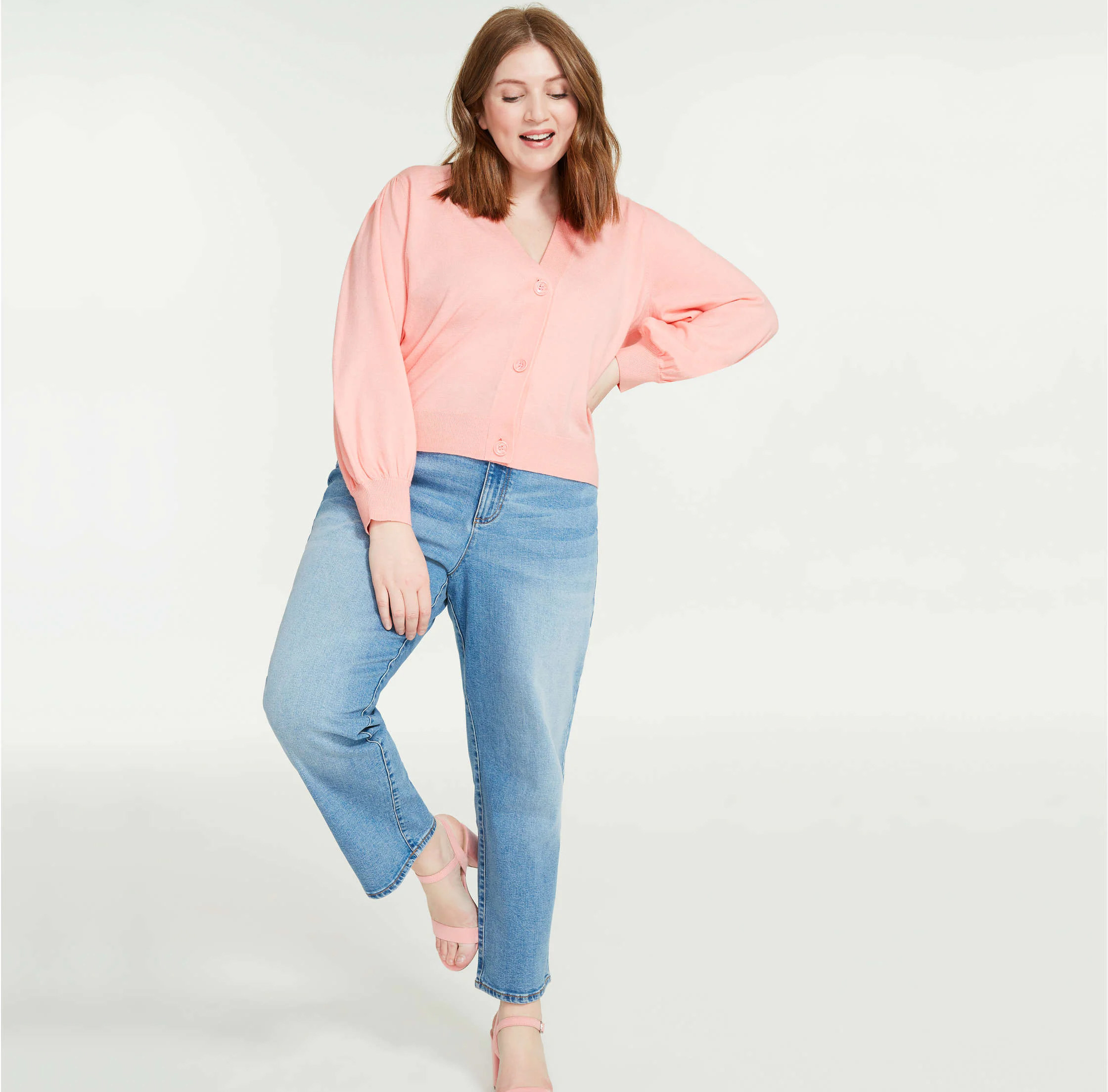 A person wearing a cardigan over a pair of jeans