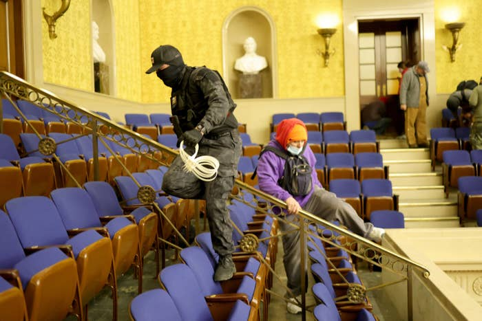 A masked man and woman climb over a railing amid rows of seats