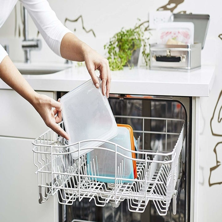 Hands putting the bag in the top rack of a dishwasher