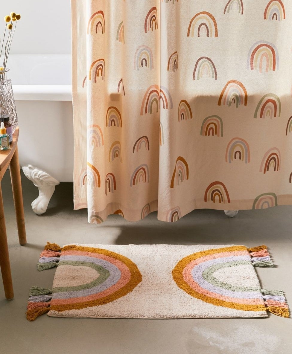 A cream colored bathmat featuring a symmetrical design with rainbows on either edge and tassel trim extending out from each strip of color