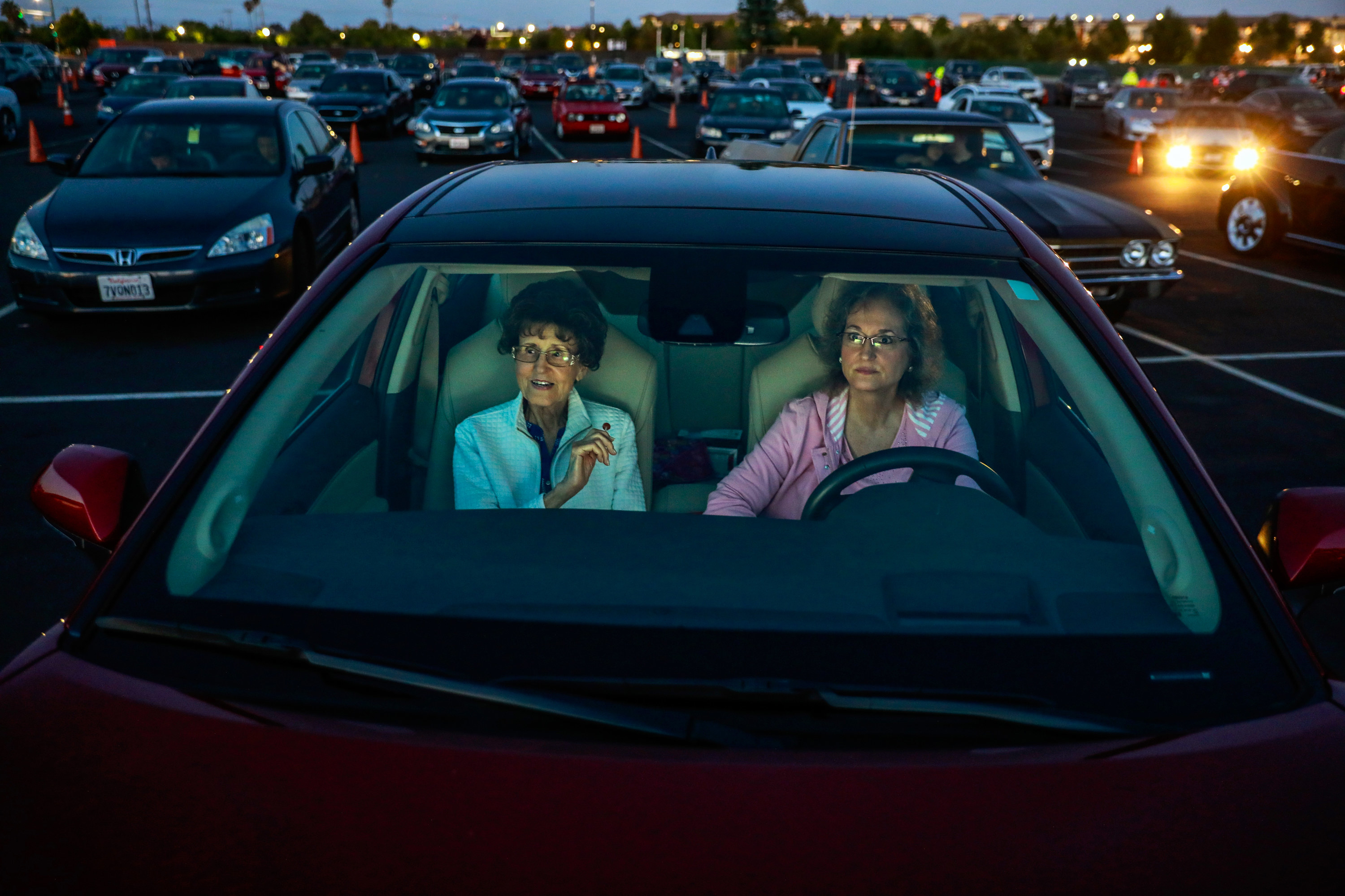 Two women in a car in a drive-in movie theater parking lot