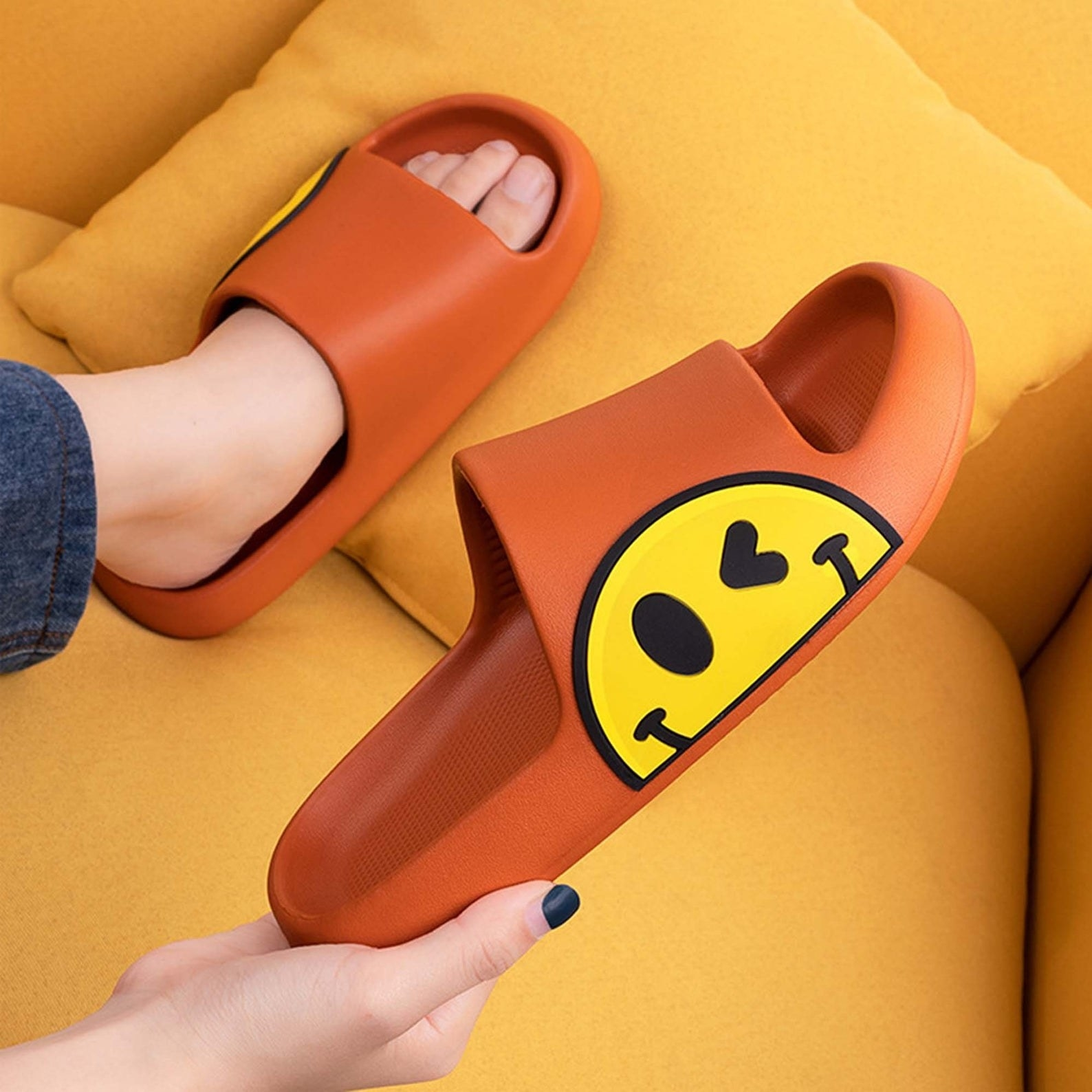 model holds pair of orange slides with graphic smiley face design on the side