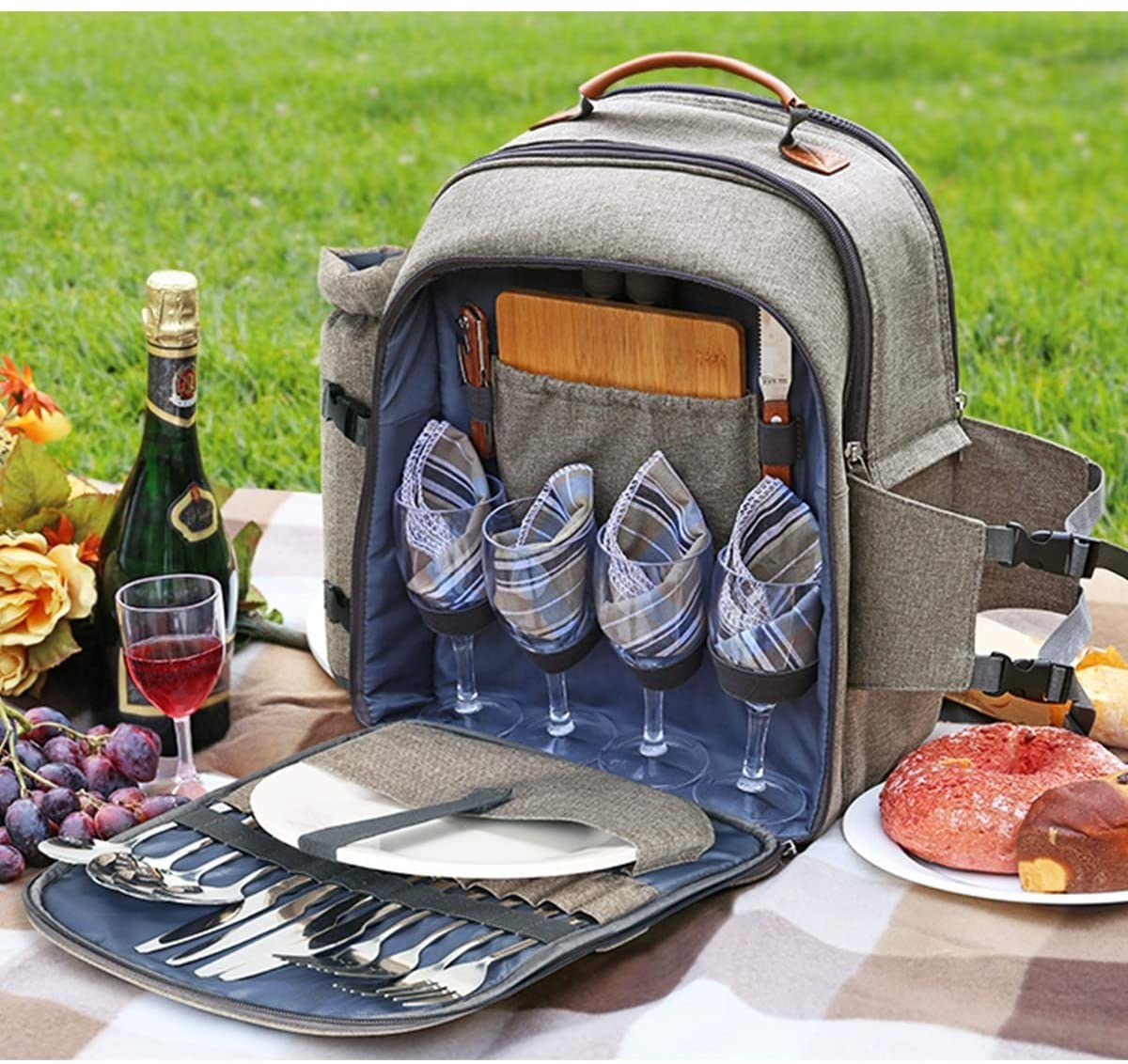 the gray and blue picnic backpack on a checked blanket in a grassy area