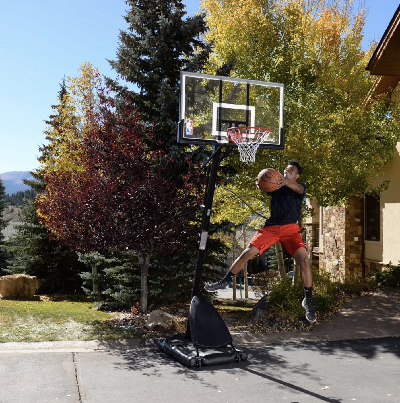 A person dunking a basketball in a hoop
