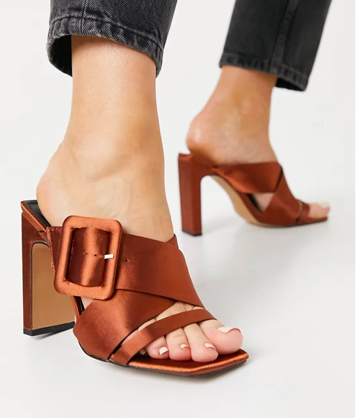 model wearing the reddish brown satin heeled sandals with a square toe and thick straps