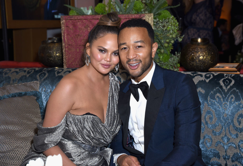 Chrissy and Teigen sitting on a couch together cheek to cheek
