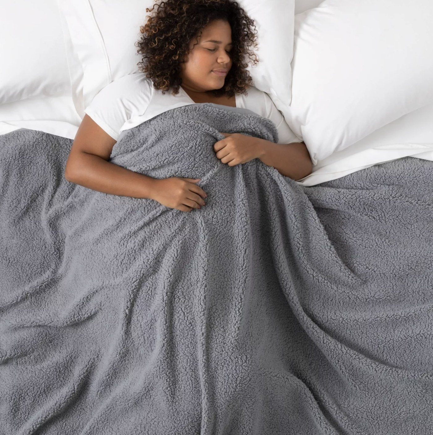 Person is laying in a grey weighted blanket on a bed