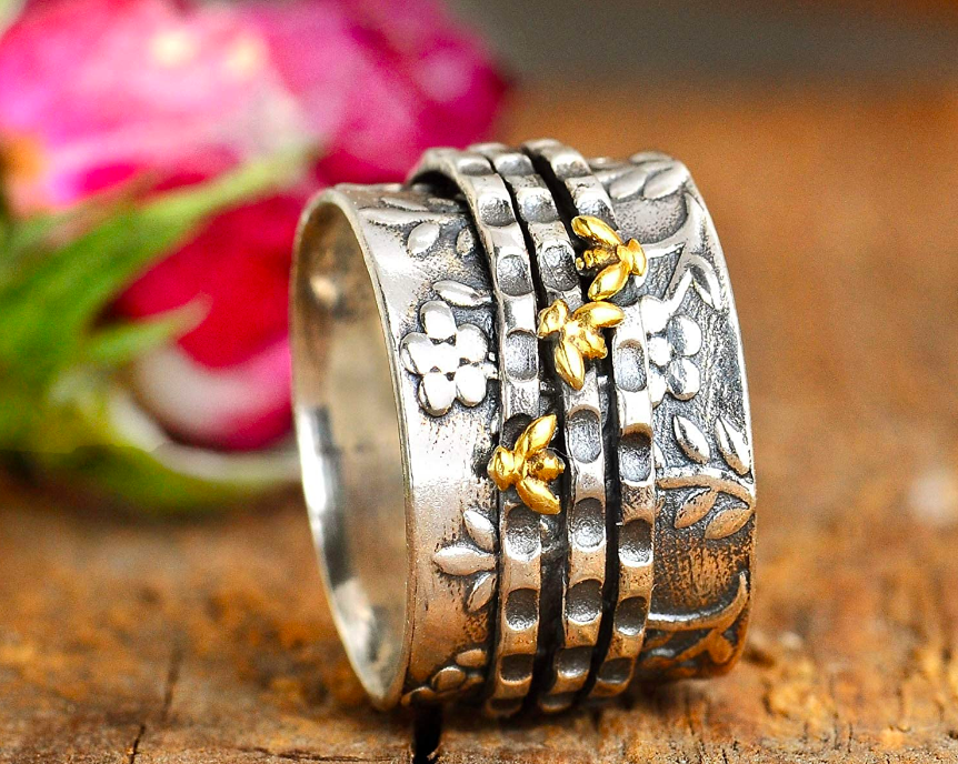 Silver band ring with floral details and three thin spinner rings with bright bee details