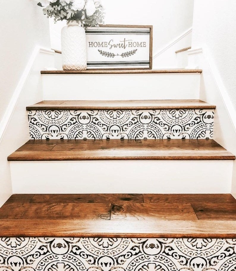white stairs with dark wood treads; ever other stair riser features a faux-distressed black geometric pattern on white
