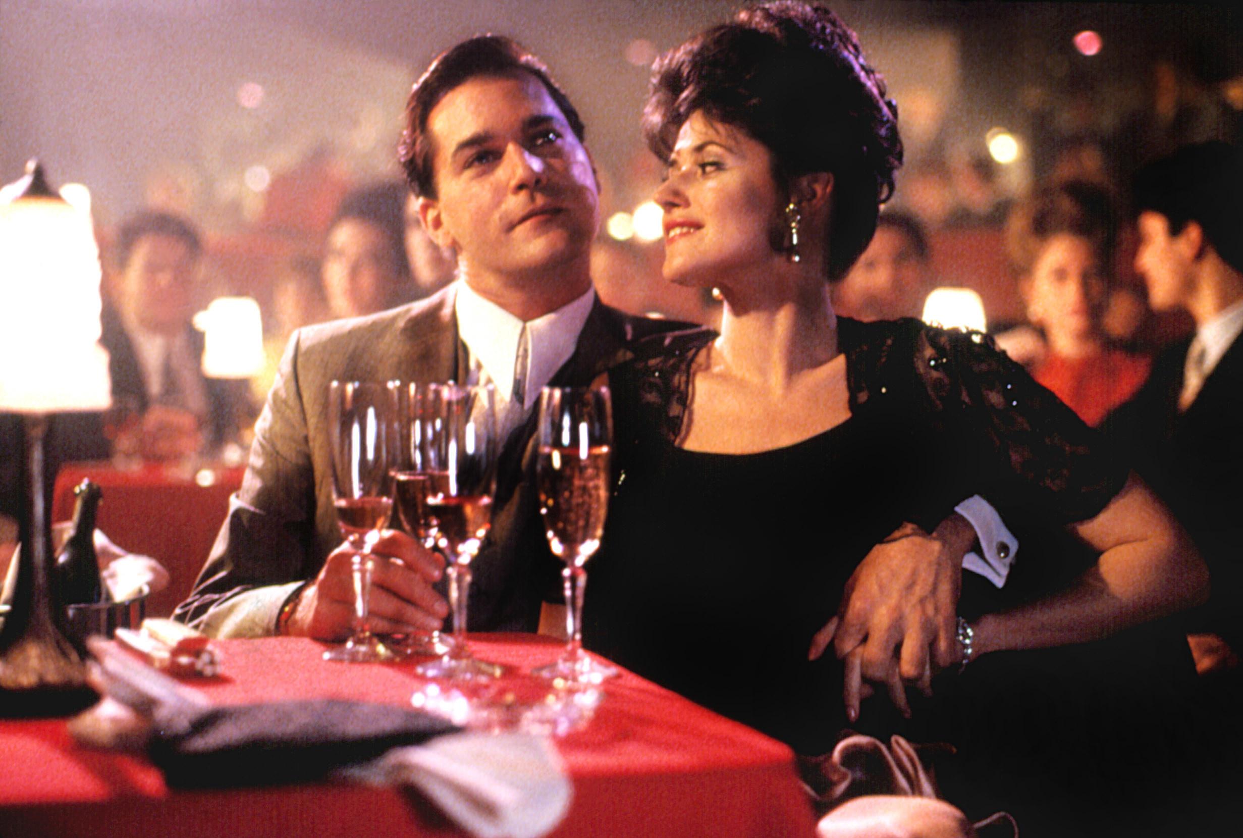 "Ray Liotta and Lorraine Bracco enjoy drinks during a scene in ""Goodfellas"""