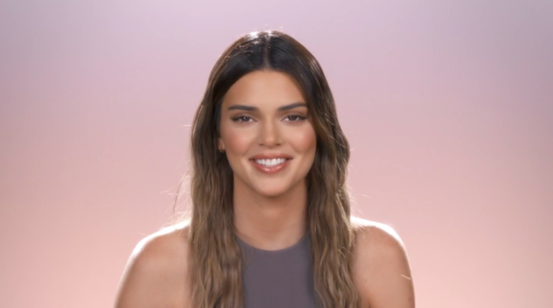 Kendall smiling in front of a pink and purple background