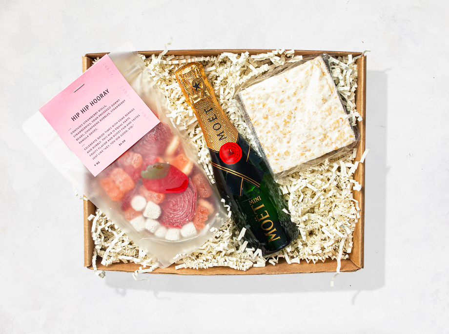 Box filled with desserts and a champagne bottle