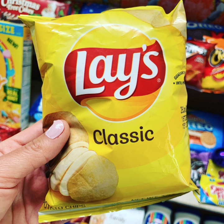 A bag of Lay's potato chips with a logo that looks like a sun and a red ribbon going across it with specific font