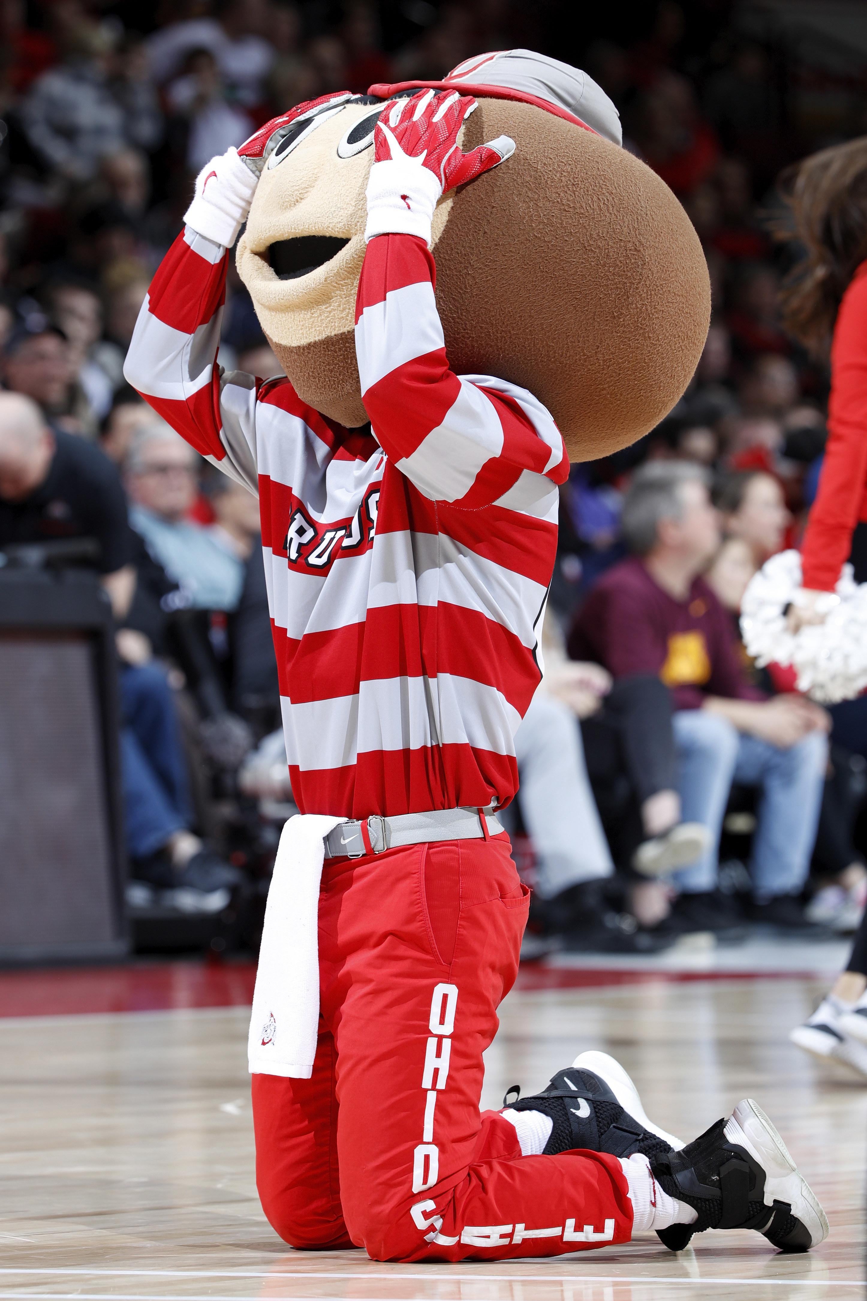 Brutus the mascot, a buckeye-head wearing a little hat, in red sweats