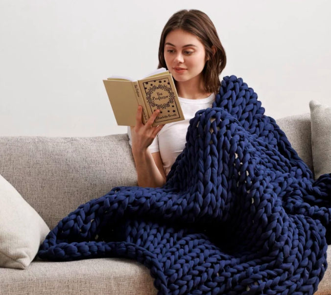 model under the navy thick knit blanket