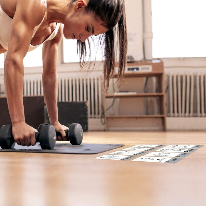 Model bends in push-up position with black dumbbells in front of line of exercise movement cards