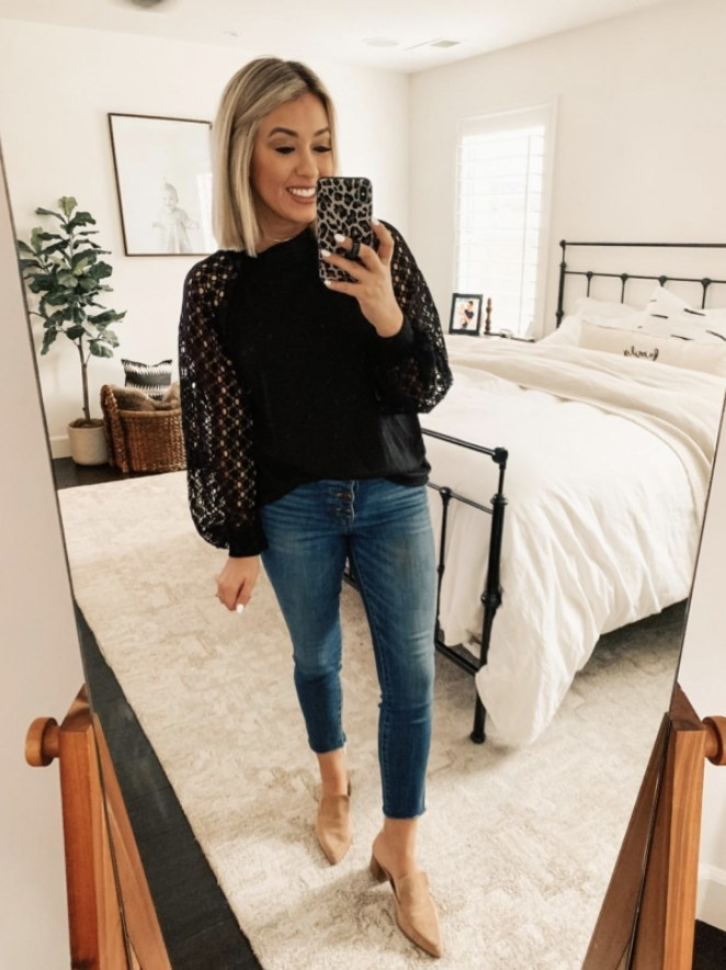 a reviewer wearing the top in black with jeans