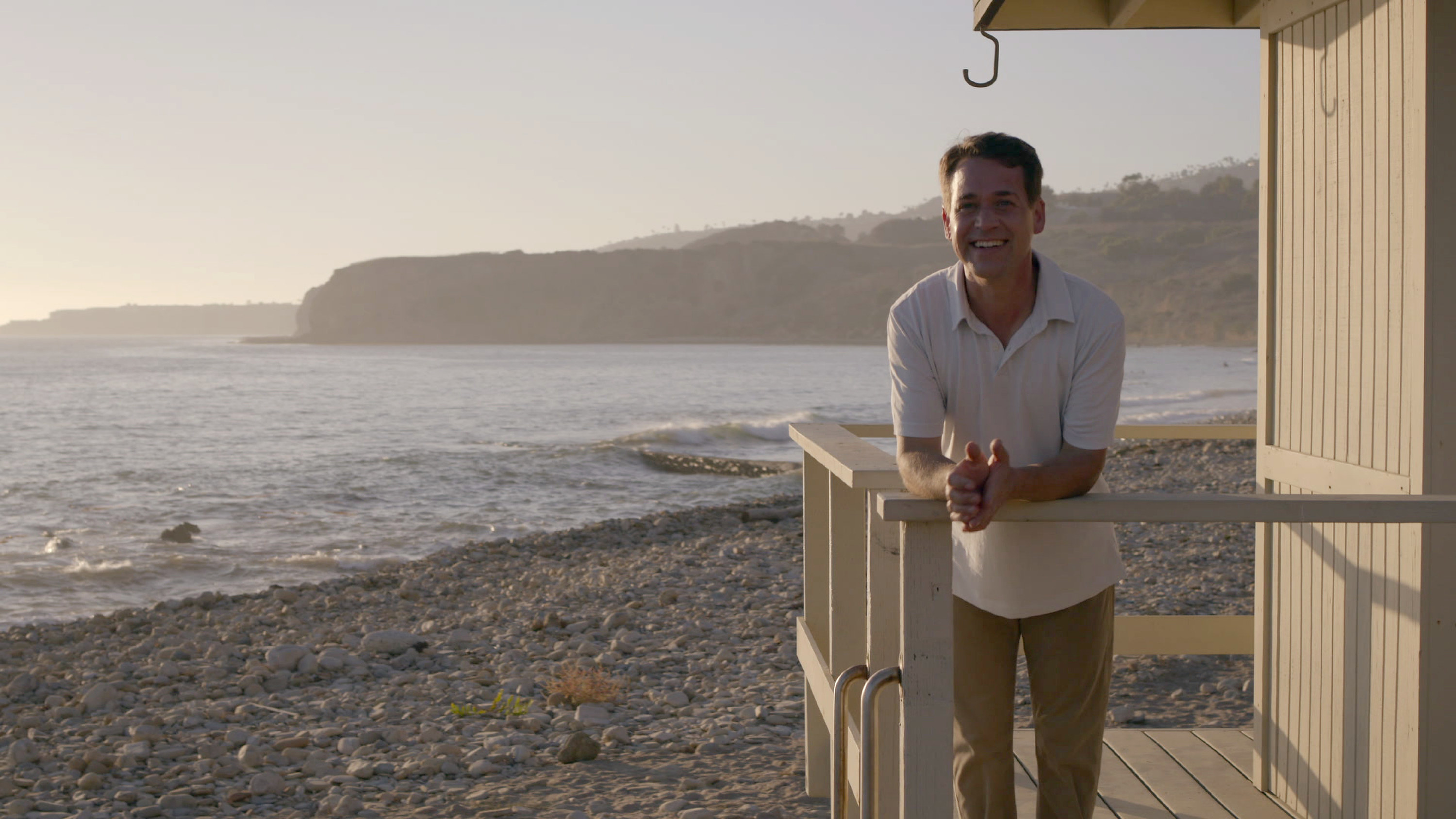 T.R. Knight stands on a porch alongside the beach in Grey's Anatomy