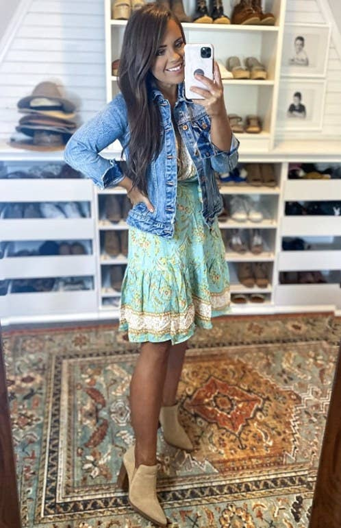 a reviewer wearing the dress with a denim jacket and booties