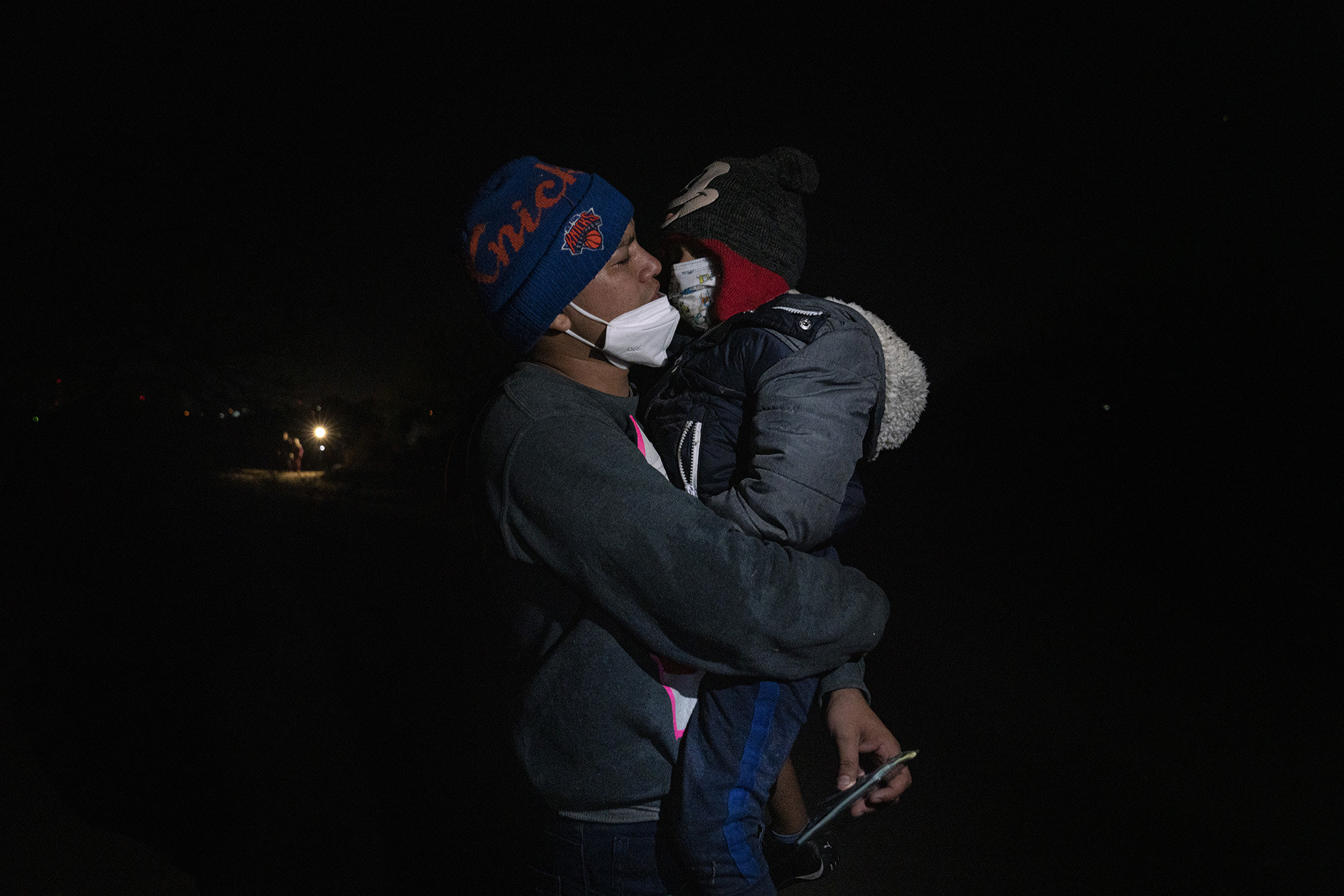 A father holds his son, both dressed in beanies, face masks, and warm clothing at night