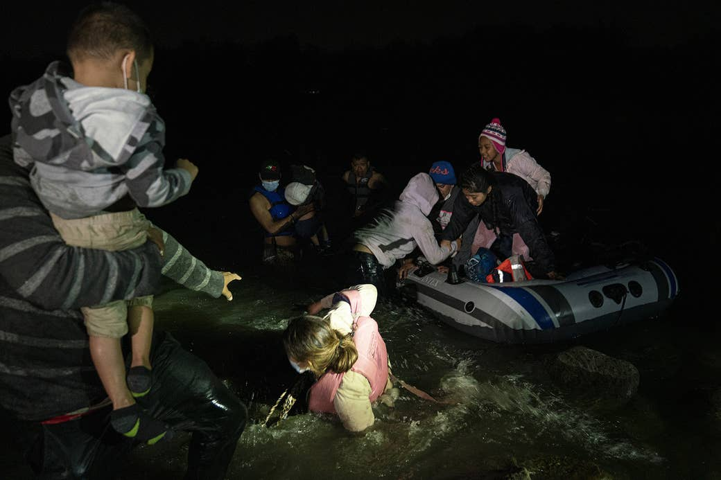 A woman lies in river rapids between her husband, who holds a young chlid and reaches out for her, and an inflatable raft carrying asylum-seekers