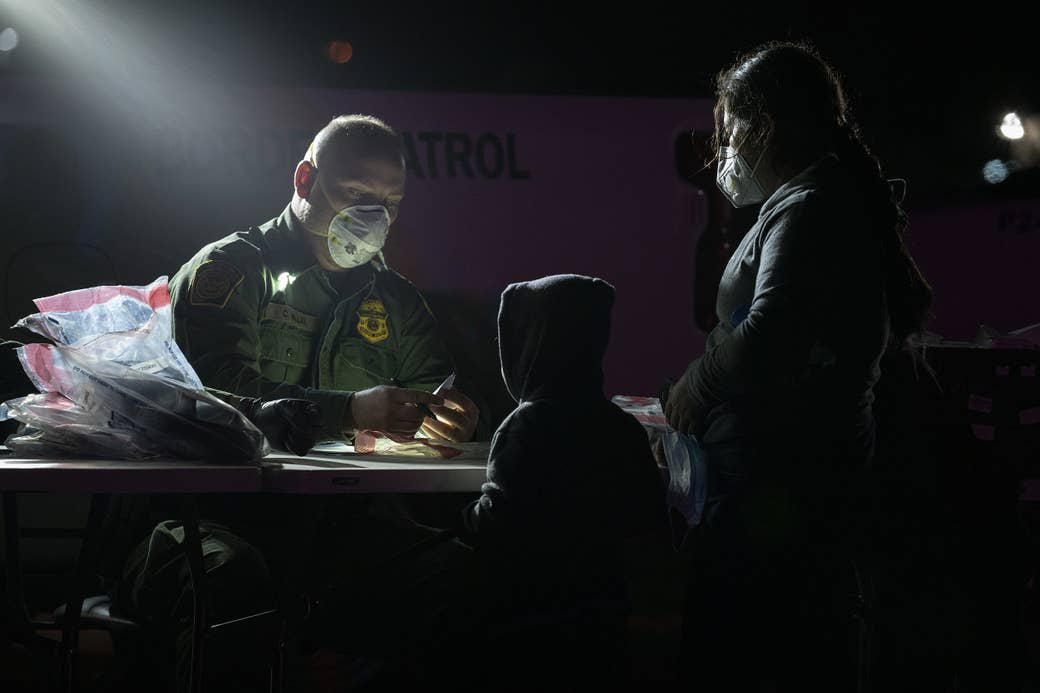 A mother and child stand by a table, where a sitting Border Patrol agent holds a pen and document in his hands