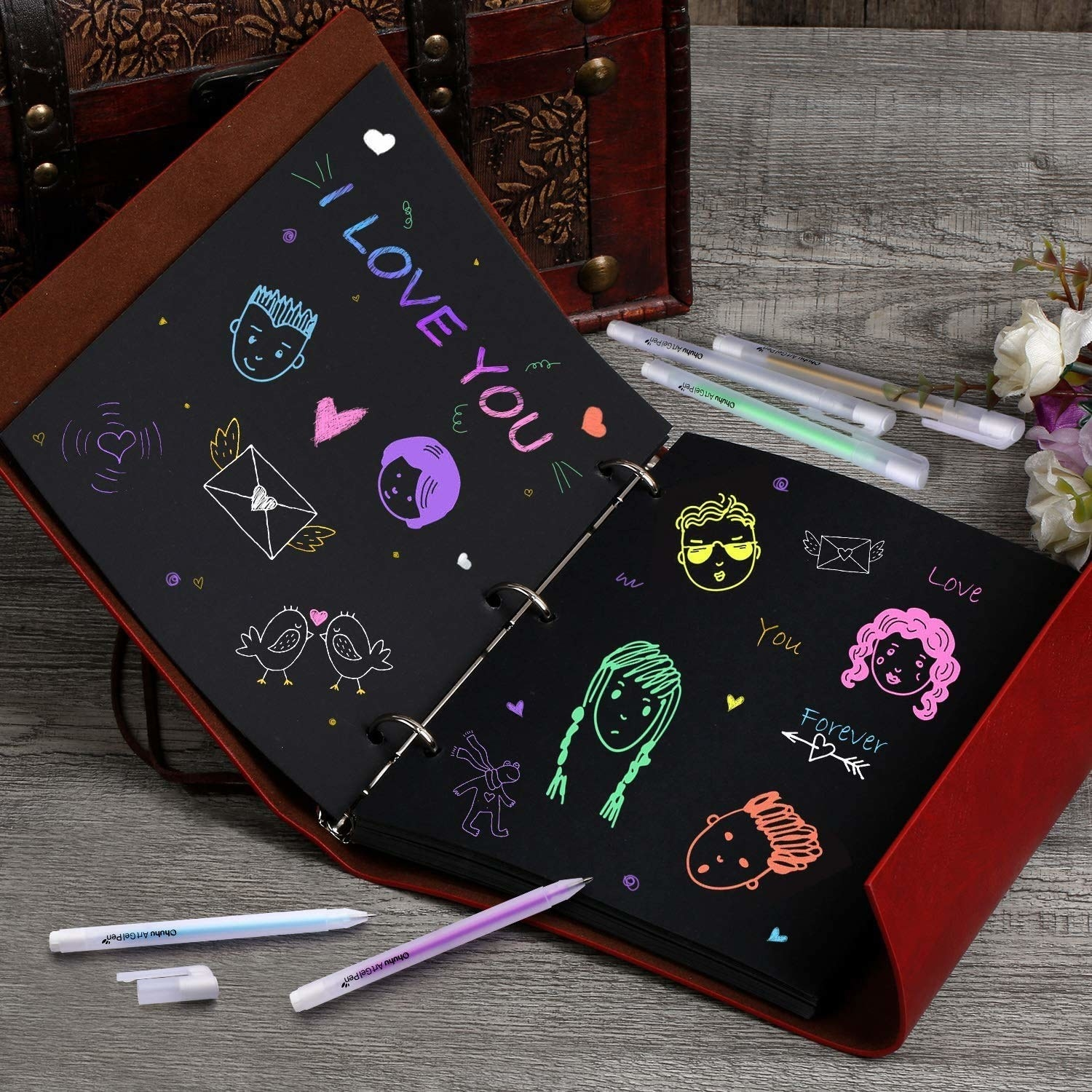 A notebook with black pages filled with colourful drawings created with the gel pens.