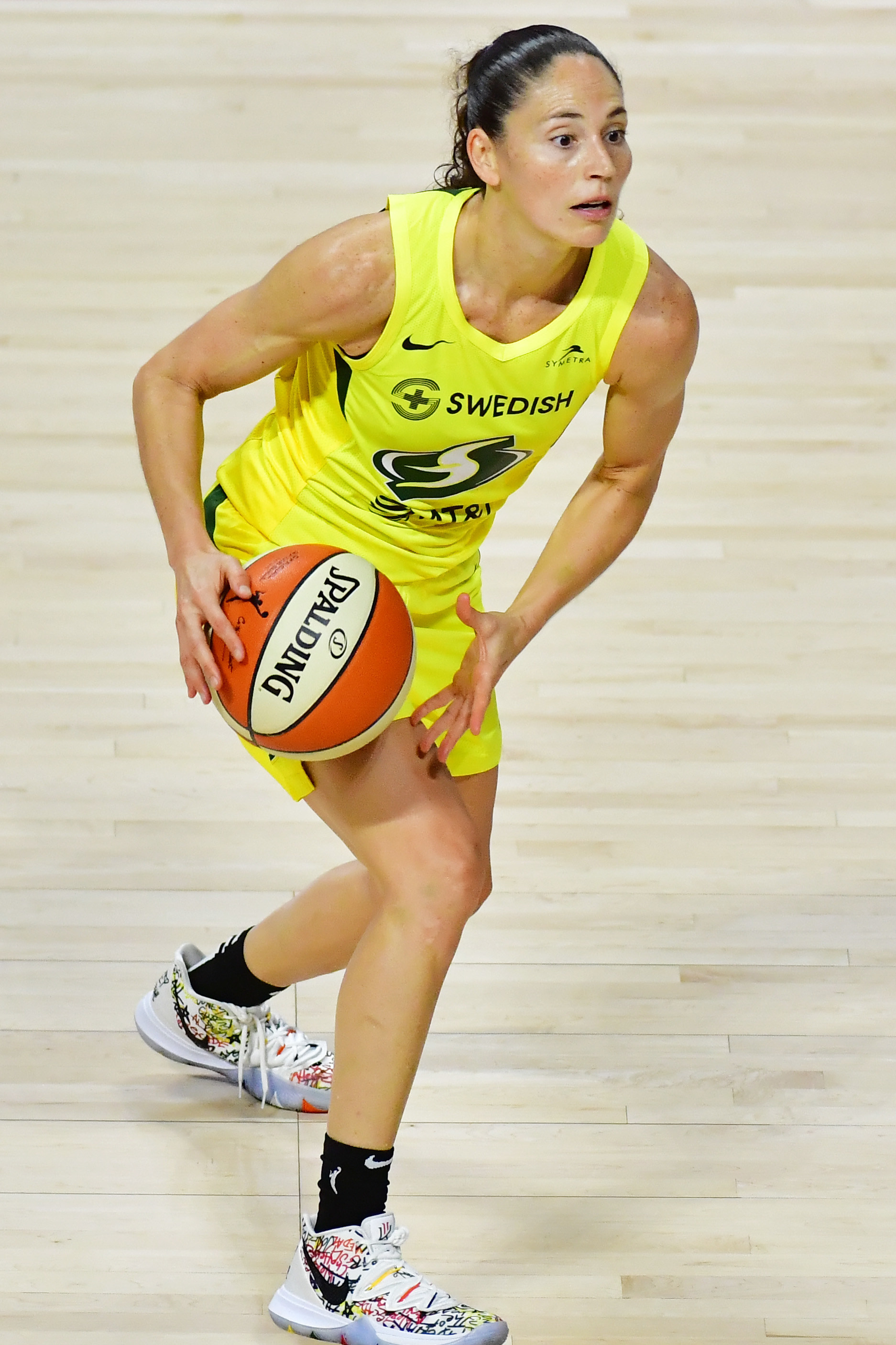 Present day Sue Bird playing basketball in Seattle Storm uniform.